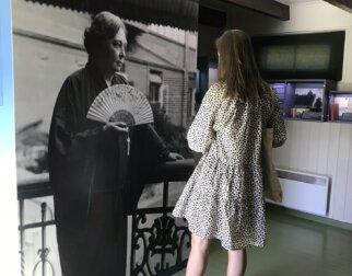 """Dame som ser på et bilde av Sigrid Undset i utstillingen """"Det er fornyes man skal"""" på Bjerkebæk, Lillehammer."""