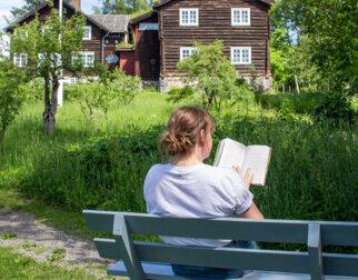 Dame som leser bok på en benk i hagen til Sigrid Undset på Bjerkebæk.