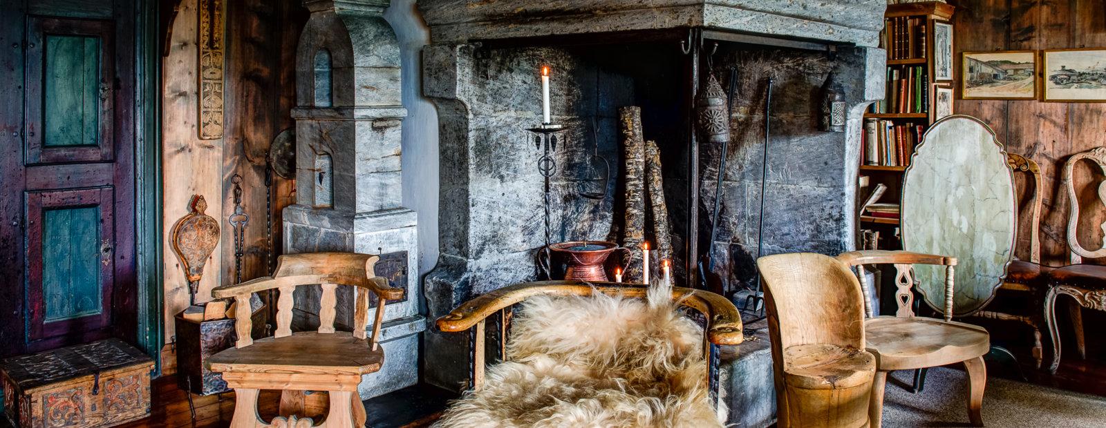 Peisestua i Sigrid Undsets hjem Bjerkebæk med gammel peis med forskjellige trestoler rundt, den ene med saueskinnsfell i.