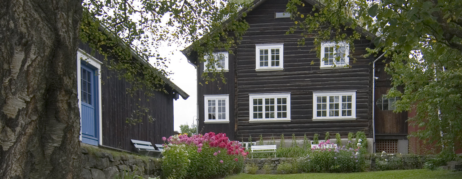 To brune tømmerhus med fargerike blomster i forgrunnen.